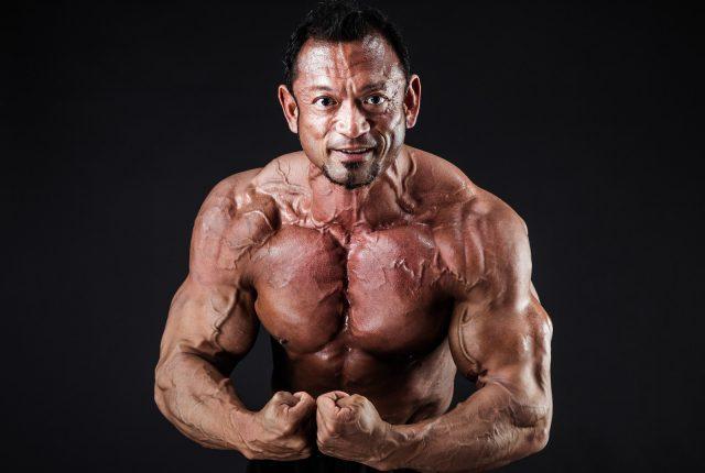 筋肉の隆起を見せつけるボディビルダー