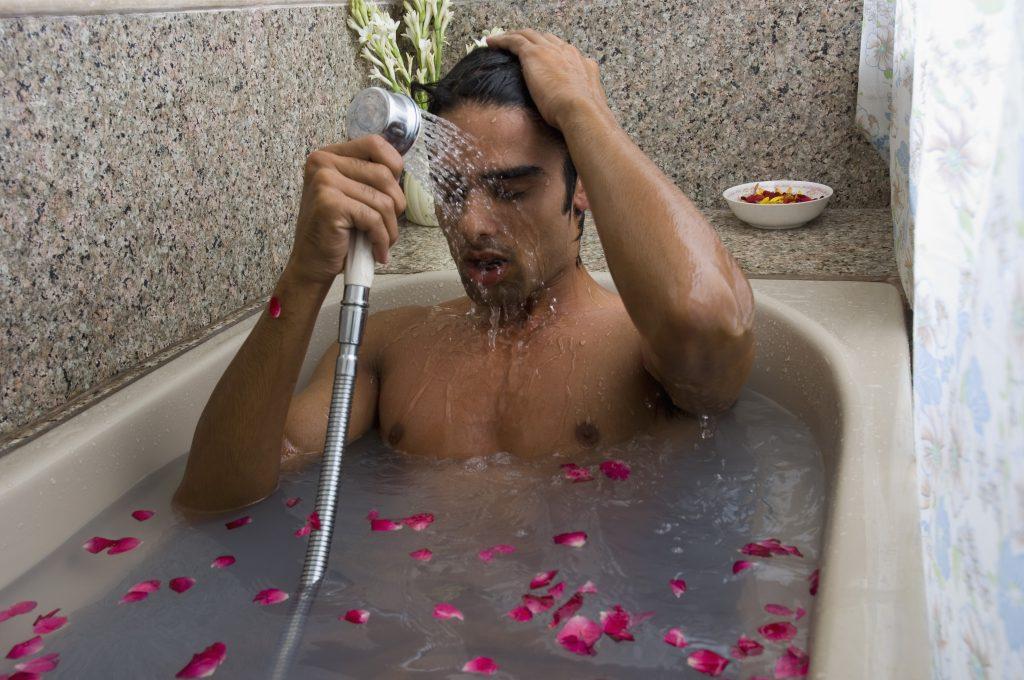 バスタブでシャワーを浴びる男性