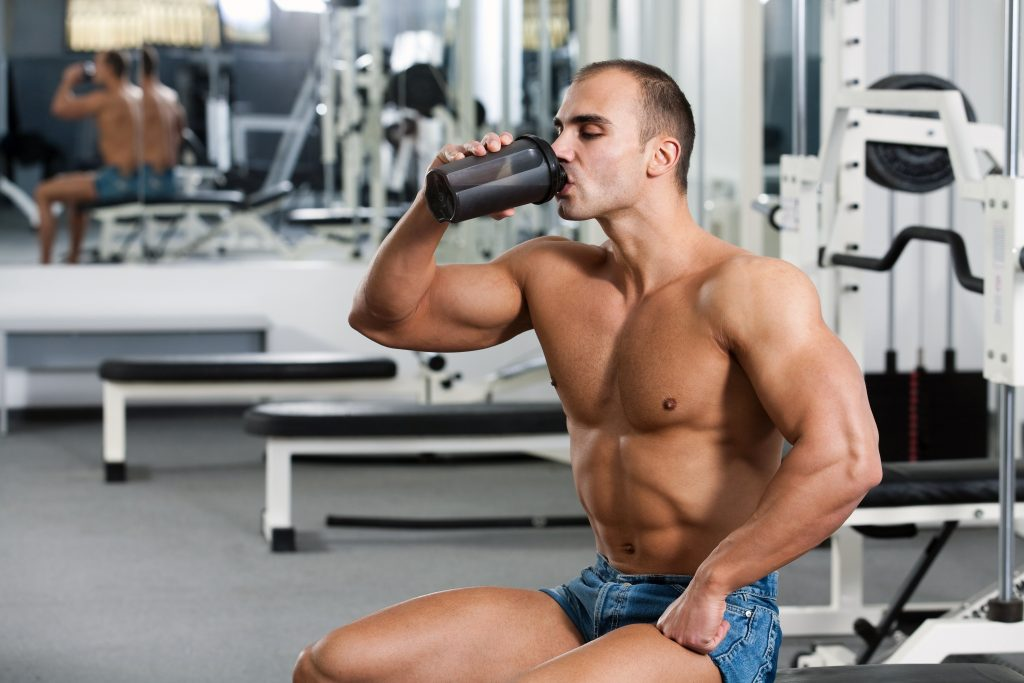 young caucasian bodybuilder in the gym, drinking a protein shake