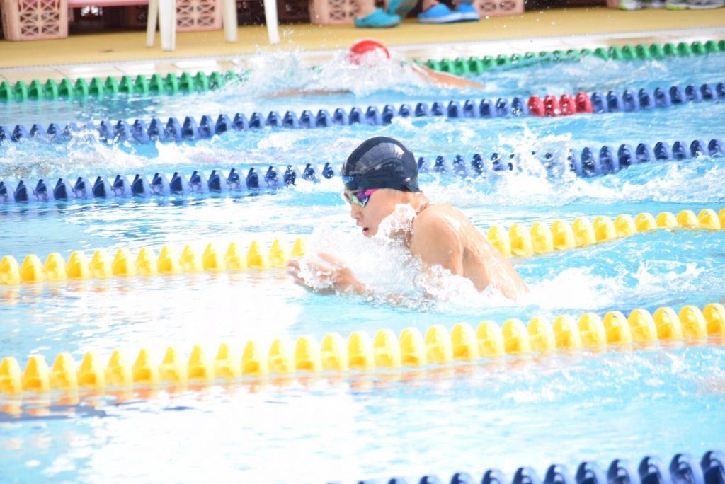 プールでバタフライを泳ぐ男性
