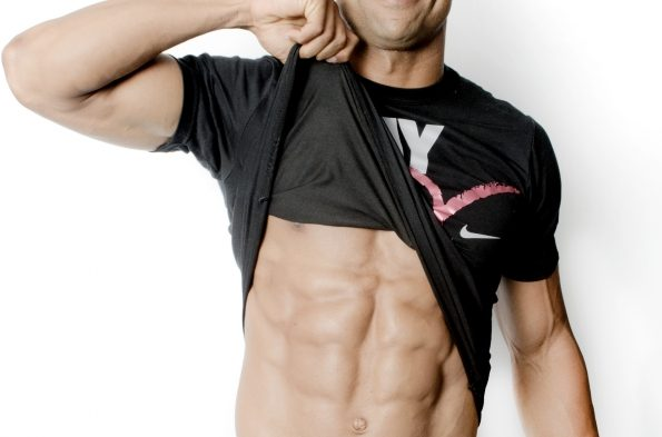シャツをめくりあげ腹筋を見せつける男性