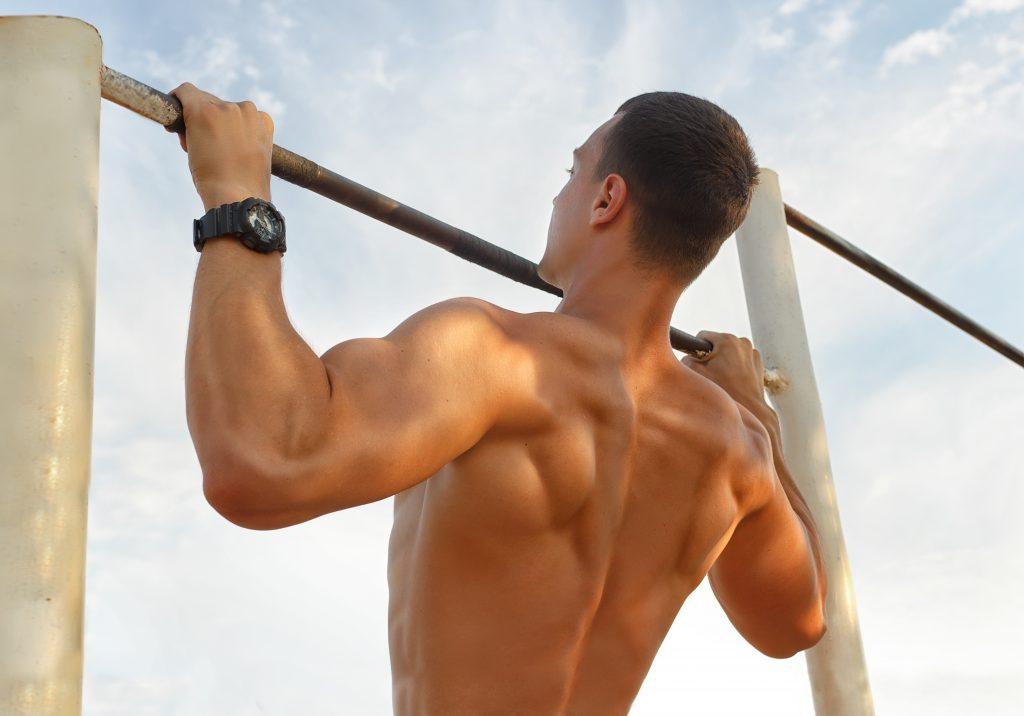 屋外で懸垂する男性