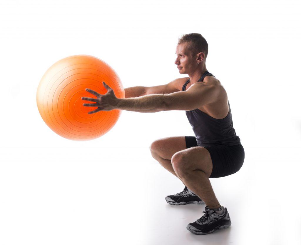 ピラティスボールを手にスクワットする男性
