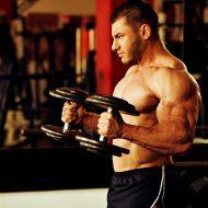 ジムでダンベルトレーニングする外国人男性