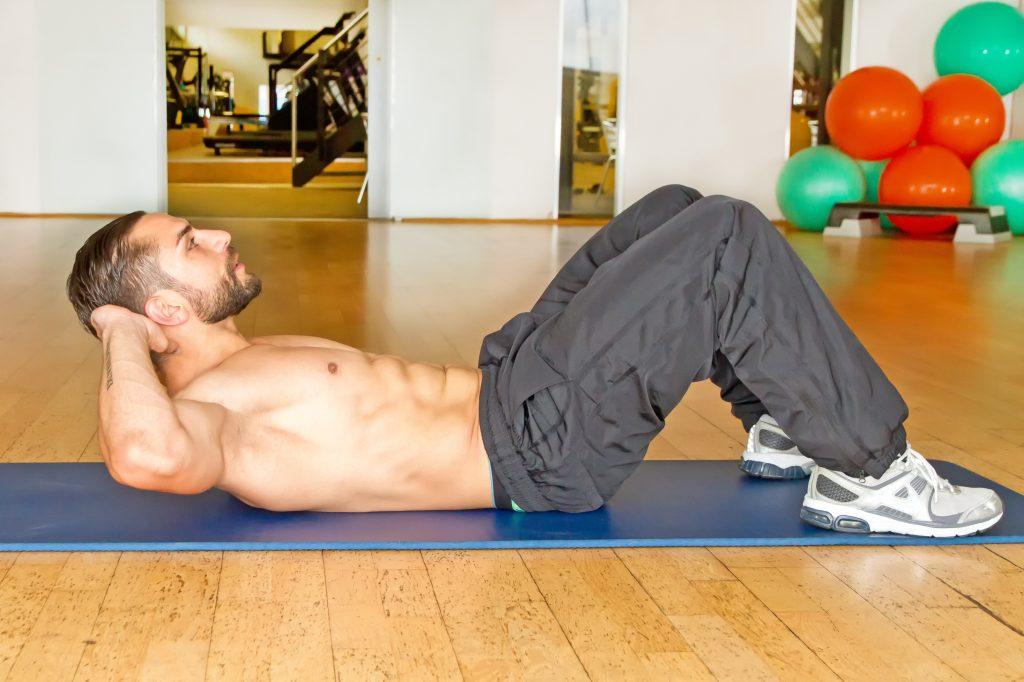 ジムのトレーニングエリアで腹筋する男性