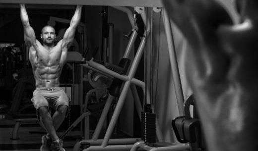 若い男が脚をぶら下げを実行する運動を発生させます - 最も効果的な Ab の 1 つは運動