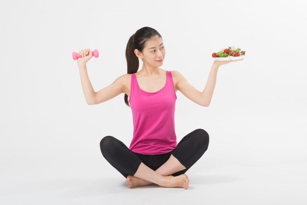 サラダを手にダンベルトレーニングするダイエット中の女性