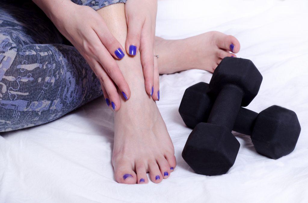 脚をマッサージする女性とダンベル