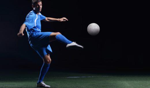 黒の背景上に分離されてサッカー スタジアムのフィールド上のボールをキックしているサッカー選手