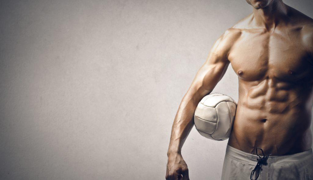 灰色の背景上にボールを持つ筋肉の若い男