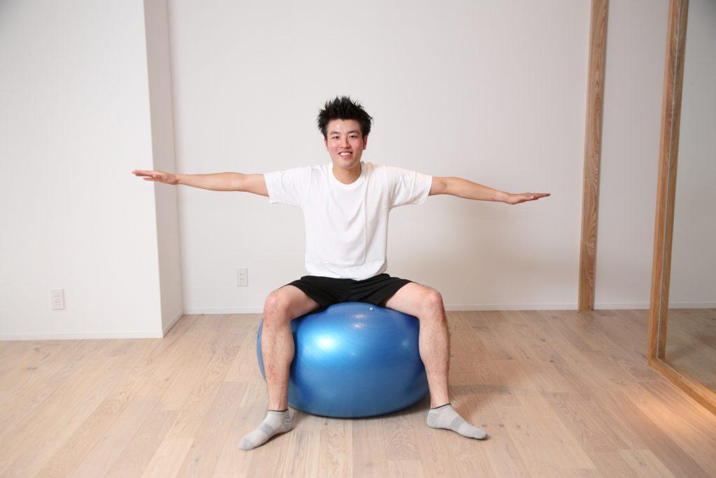 バランスボールに座っている男性