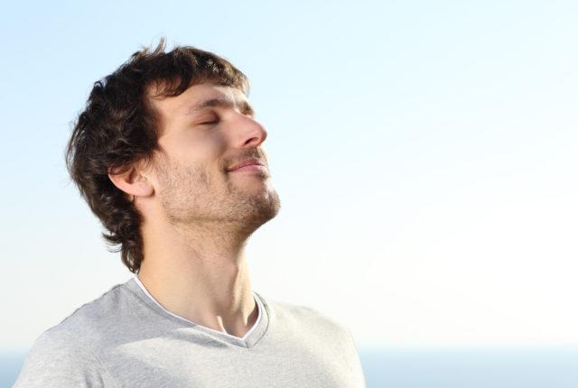 肩甲骨をほぐすために深呼吸するハンサムな外国人男性