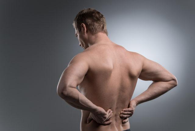 背中の痛みと上半身裸の若い男のクローズ アップ。灰色の白い背景の上に立っている若い男