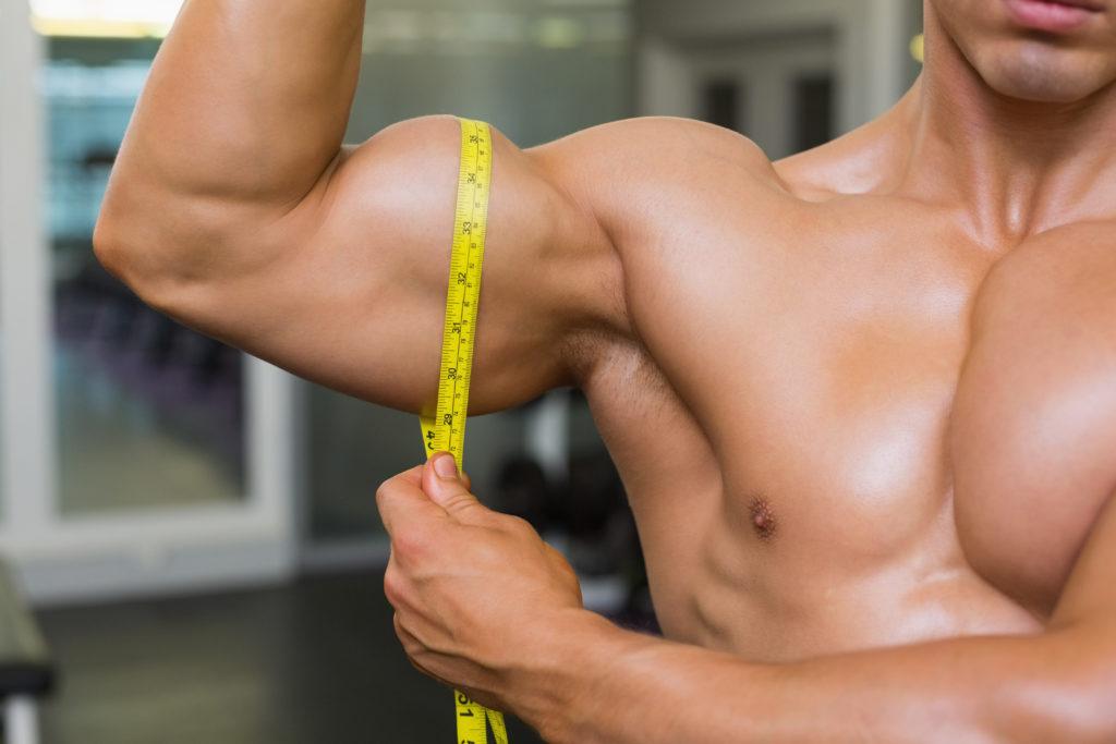 測定ジムで上腕二頭筋筋肉の男のセクション半ばのクローズ アップ