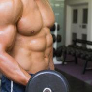上半身裸の若い筋肉男ジムでダンベル運動の中間セクション