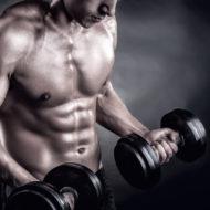 暗い背景にウェイトを持ち上げる筋肉青年のクローズ アップ