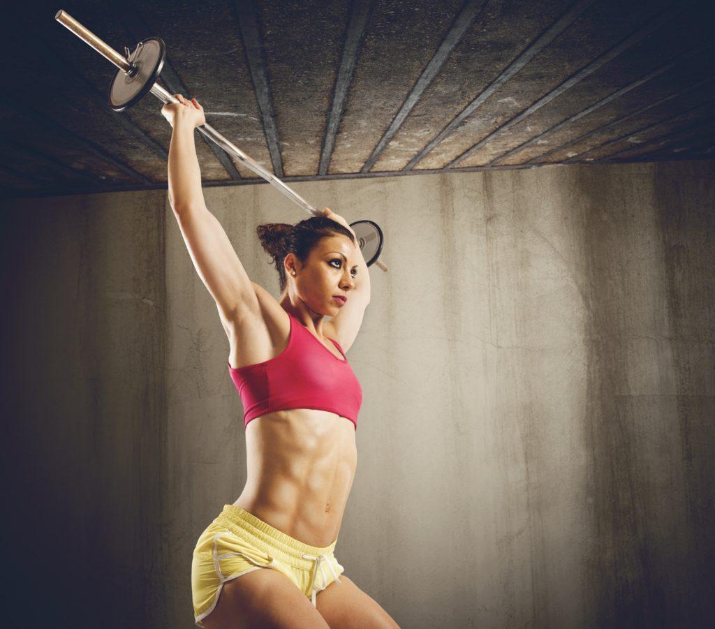 バーベルでハード トレーニングを行って筋肉女