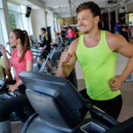ランニングマシーンでトレーニング中の笑顔の男性