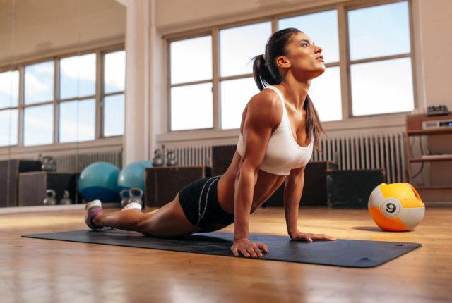 女性フィットネス マット コア ストレッチを行います。ジムでストレッチ運動を行う筋肉の若い女性。