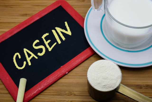 カゼインは、牛乳のカップとウッドの背景に粉ミルクのスクープで黒板に書かれて