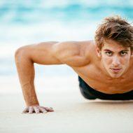海辺で腕立て伏せをする外国人男性