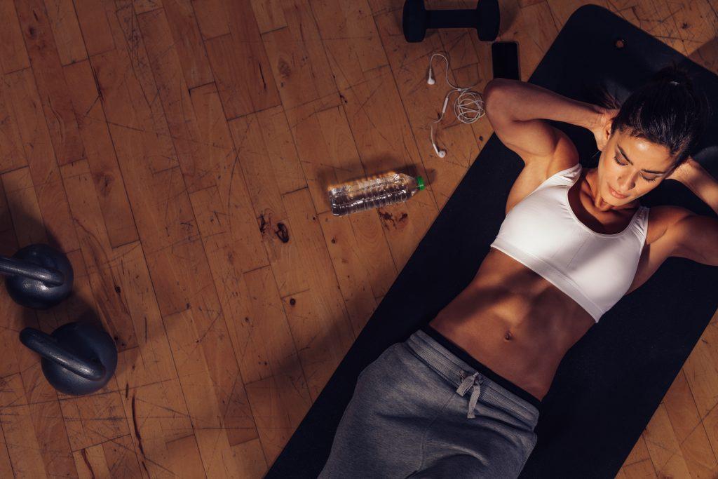 ジムで腹筋トレーニングを行う女性の俯瞰。筋肉若い女性の胃の演習を行う頭の後ろに両手運動マットの上に横たわる。