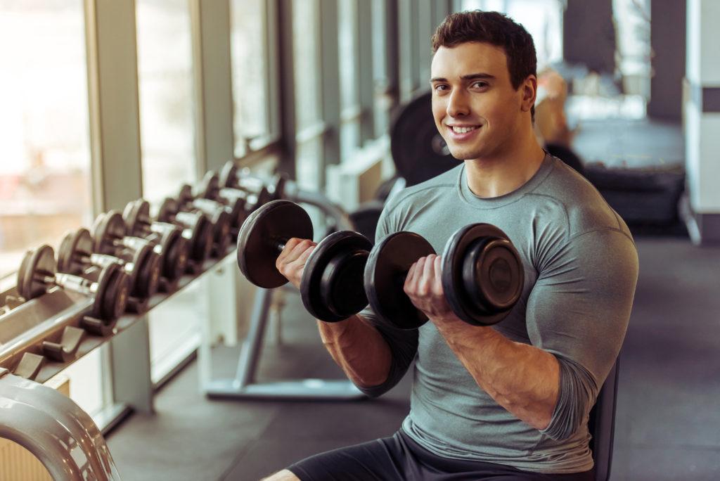 ジムでダンベルトレーニングをする外国人男性
