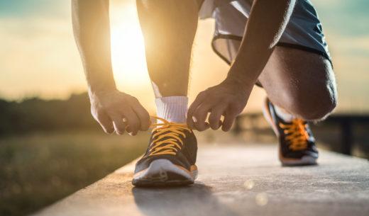 靴ひもを結ぶウォーキング中の男性