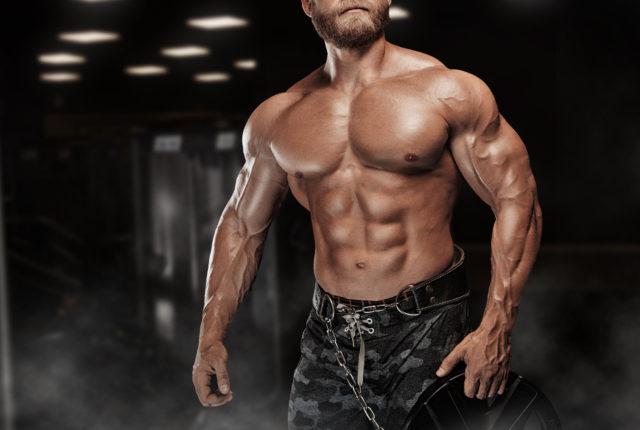 ジムで練習後ポーズをとって筋肉運動ボディービルダー フィットネス モデル