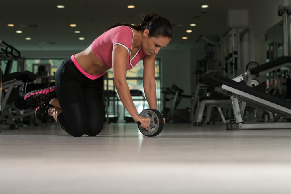 魅力的な女性はジムの床に Abs の車輪ローラー運動フィットネス トレーニングの一環として