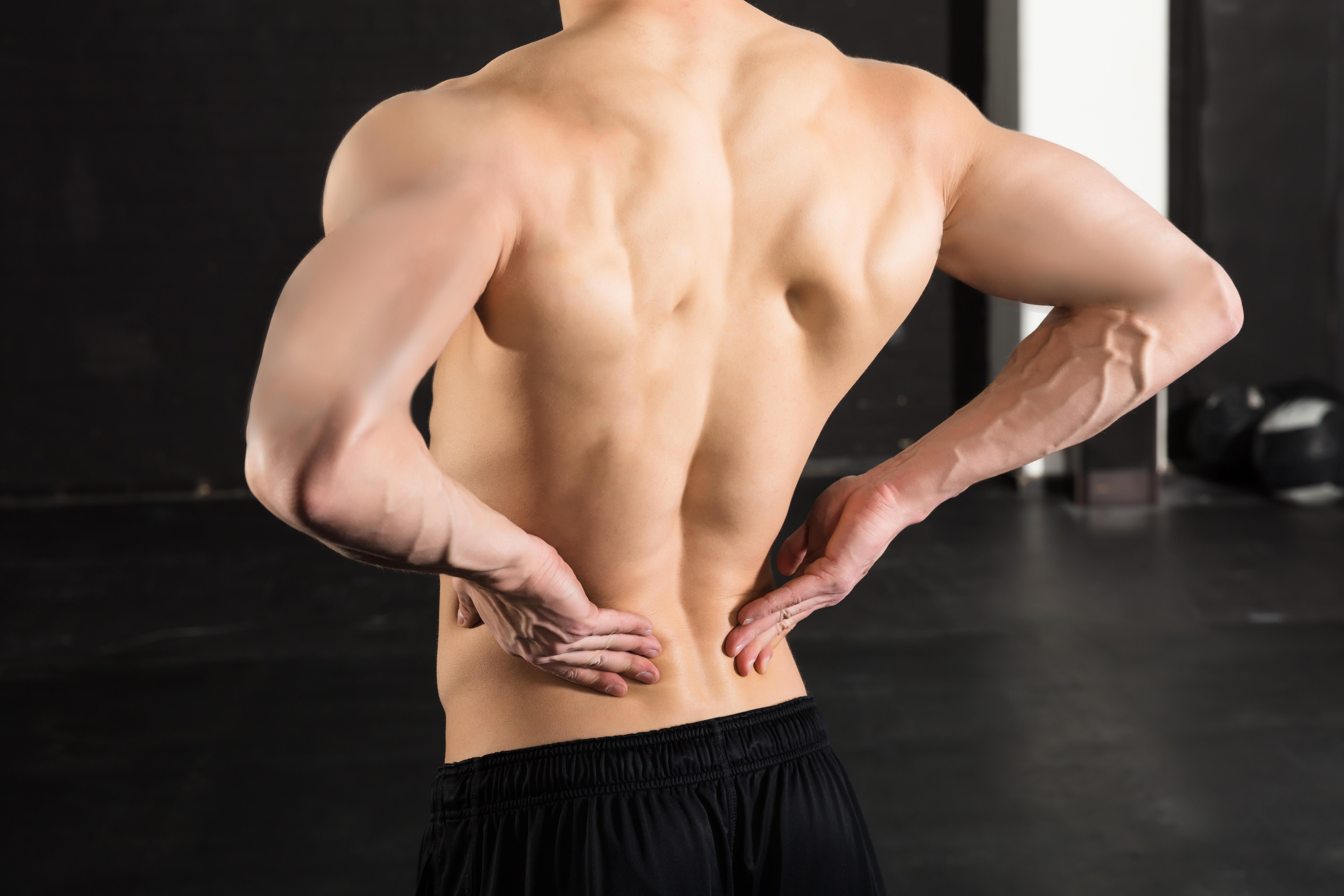 腰に痛みをかかえる筋骨隆々の男性