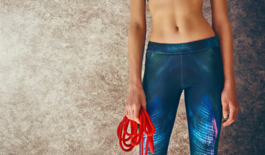 健康的なライフ スタイルとスポーツの概念。ファッショナブルなスポーツウェアの女性は縄跳びで運動を行っています。