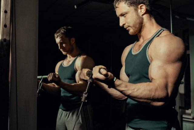スポーツジムで筋力トレーニング中の男性