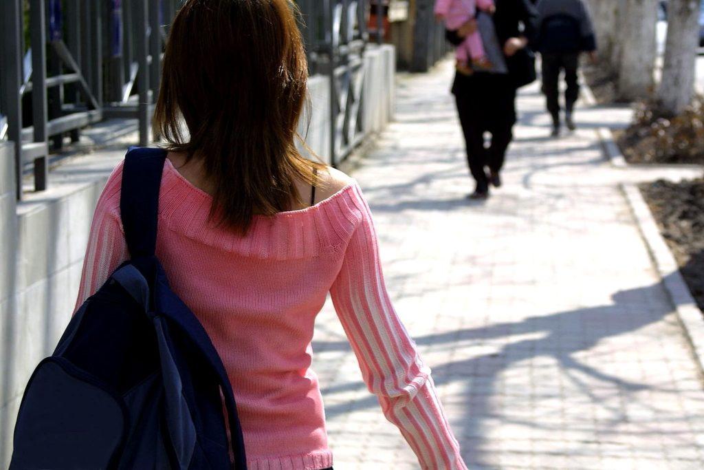 カバンを提げて歩く女性