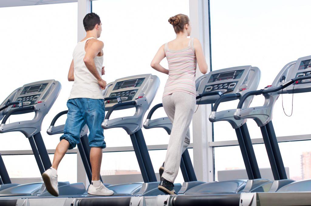 若い女とジムの運動で男。マシン上で実行します。
