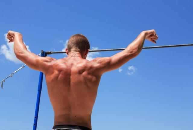 青空の下、鉄棒の前に立った逞しい広背筋の男性