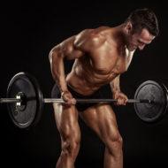 ボディービルダーの筋肉男が黒の背景上の大きなダンベルのエクササイズ