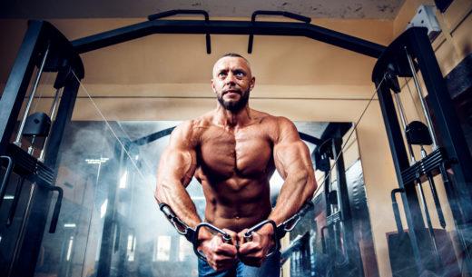 ケーブルクロスオーバーでのトレーニングに励む男性