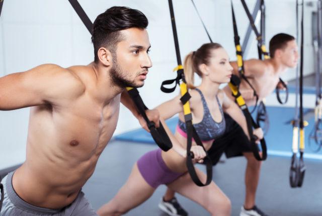 ジムで筋力トレーニング(TRX)を行う男女
