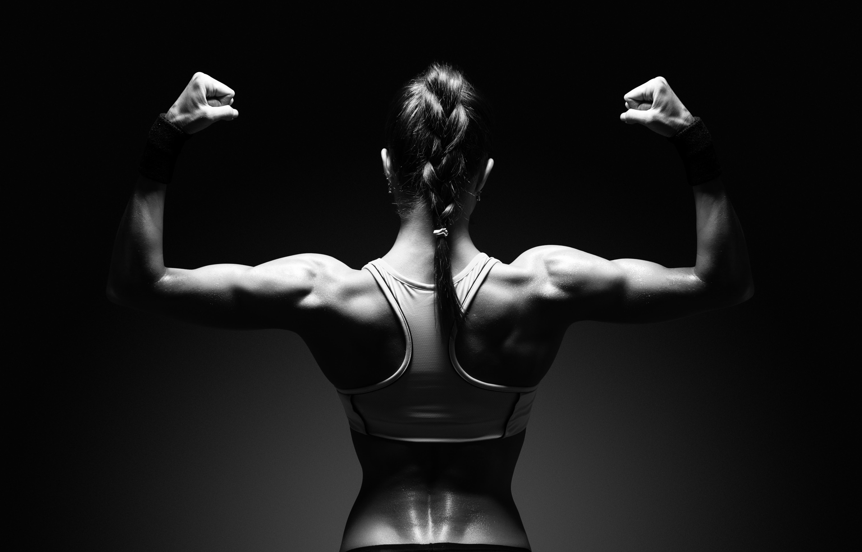 背中の筋肉を示す運動若い女性