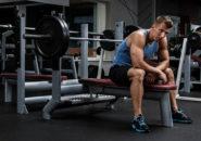 筋トレ器具の上に座る男性