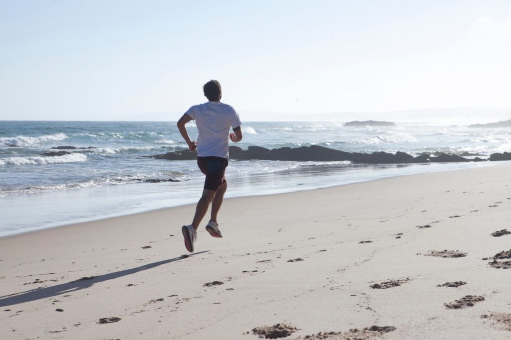 海辺を走る男性