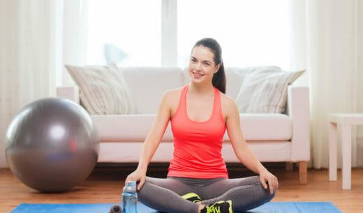 スポーツ用品自宅でマットに座っている 10 代の少女の笑顔