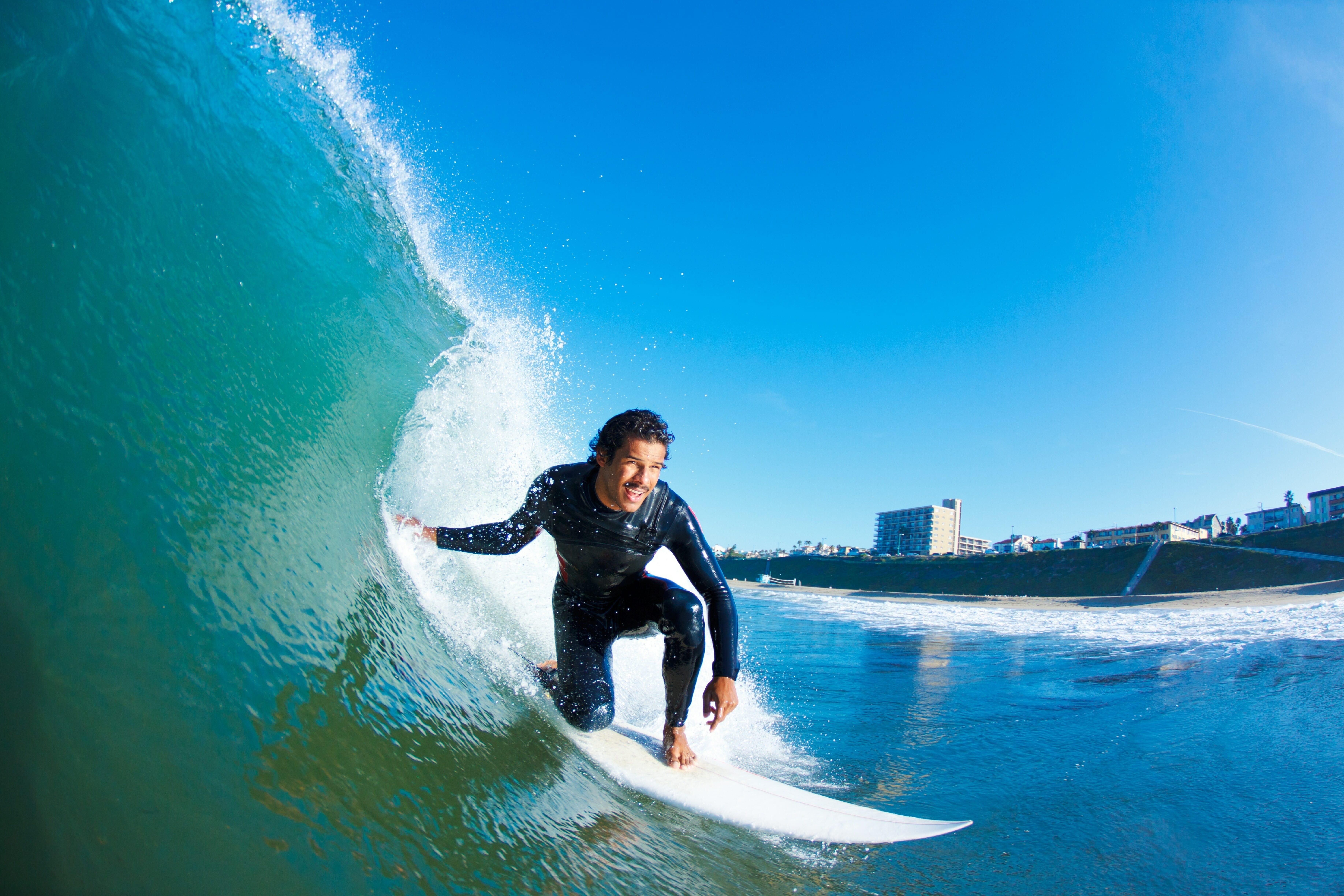 青い波でサーフィンする男性