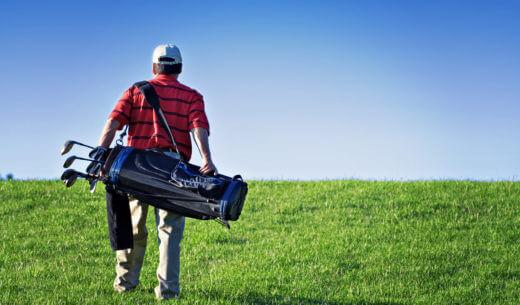 ゴルフコースを歩く男性