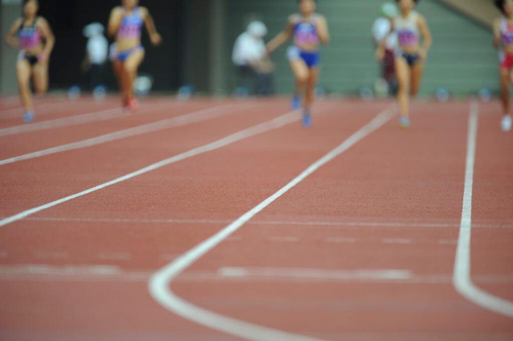 陸上競技場で走る女性