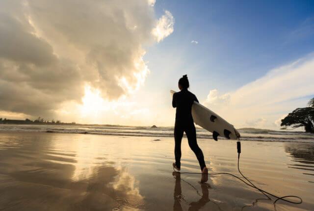 サーフィンをする女性、ビーチにいるサーファー