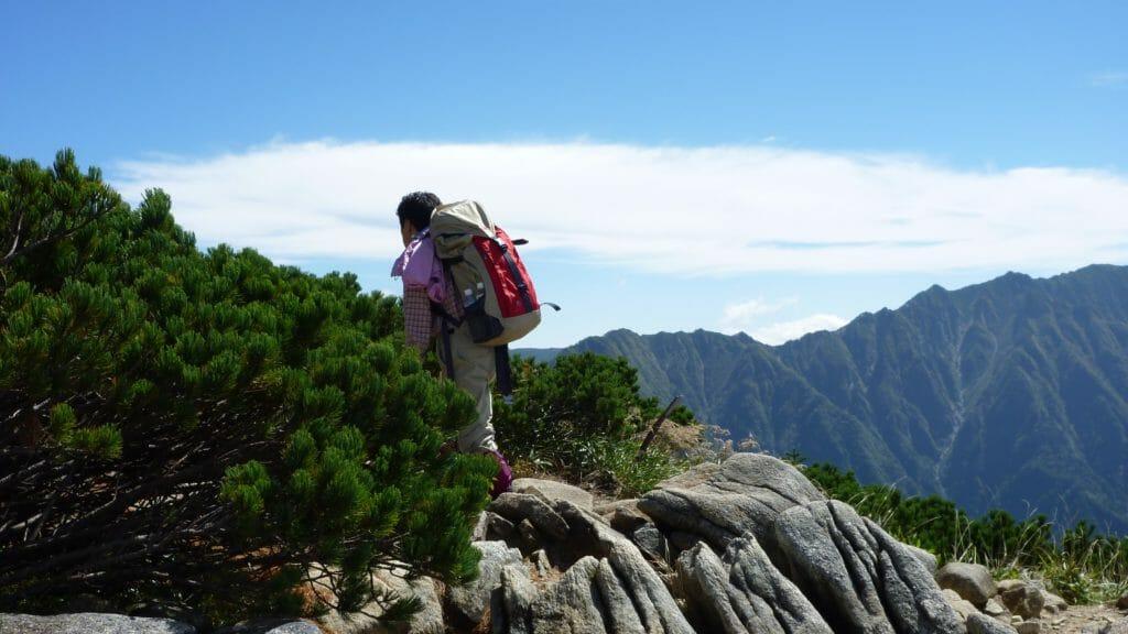山で崖の近くに立つ男性