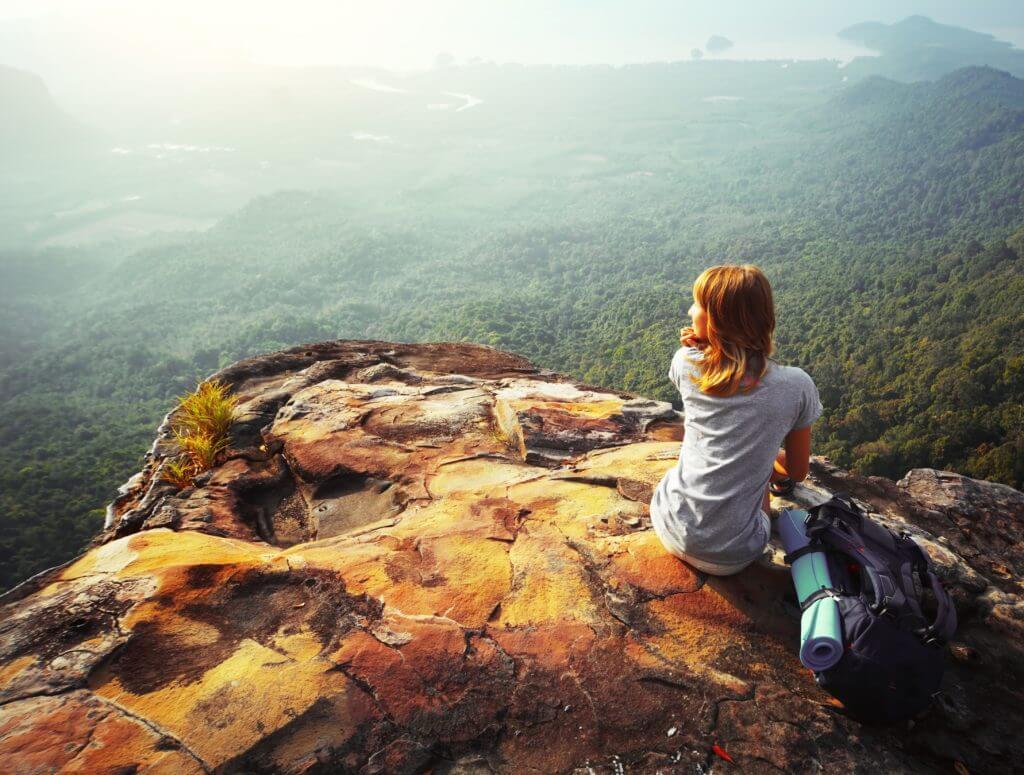 山で座り込み休憩する女性