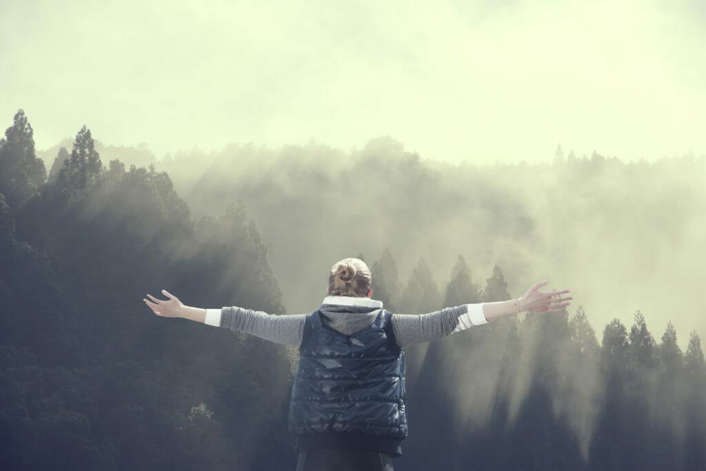 山で光を浴びる男性